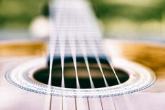 Acoustic guitar bridge and strings close up - macro royalty free stock photo