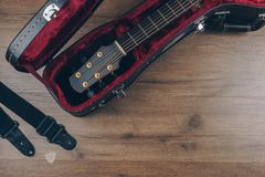 An acoustic guitar in the brown leather guitar hard case stock photo