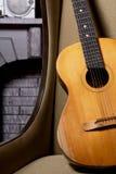 Acoustic guitar on chair against the brickwork Stock Photos