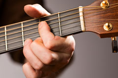Acoustic guitar chord. Close-up of acoustic guitar players left hand fingering a chord Stock Photography