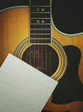 Acoustic guitar with the clean sheet of paper on a dark background Stock Image