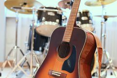 Acoustic guitar close up with drum kit in background. Brown wood acoustic guitar close up, with blurred drum set in background. Band rehearsing playing together stock images