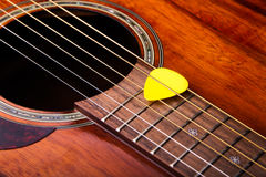 Acoustic Guitar. Close-up image of an acoustic guitar featuring soundhole, strings and fretboard with a guitar pick resting on strings Royalty Free Stock Image