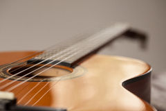 Acoustic Guitar Close Up From The Side. Close up macro of wood acoustic guitar for playing music Royalty Free Stock Photography