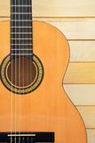 Acoustic guitar closeup view. Acoustic guitar closeup front view on wooden background stock image