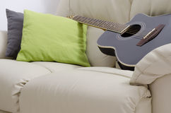 Acoustic guitar on the couch Stock Images