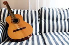Acoustic guitar on a couch Royalty Free Stock Photos