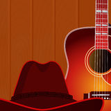 Acoustic guitar and cowboy hat against the wood wall background. Stock Photography