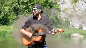 Acoustic guitar emits black smoke. Bearded Caucasian guy in a shirt, cap and sunglasses funny pretends to be playing music. A stra. Acoustic guitar emits black stock video footage