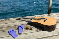 Acoustic guitar and flip flops. On a dock by the lake royalty free stock photography