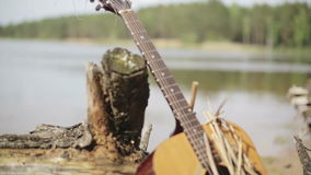 Acoustic Guitar forgotten on the shore of the lake near the old stump with roots. Close up. Acoustic Guitar forgotten on the shore of the lake near the old stock footage