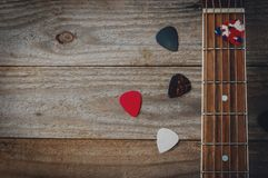 An acoustic guitar fretboard and some guitar picks on wooden table. Acoustic guitar fretboard and some guitar picks on wooden table stock photography