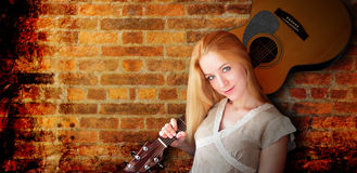 Acoustic Guitar Girl Abstract Brick Background. A young, blond girl is holding an acoustic guitar. There are shadows and she is standing against an abstract Stock Images