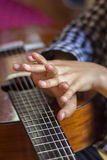 Acoustic guitar and girl's's hands Royalty Free Stock Images