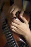 Acoustic guitar and girl's's hands Stock Image