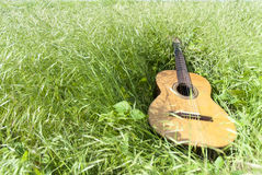 Acoustic guitar in the grass field. Acoustic guitar in the green grass field Stock Photography
