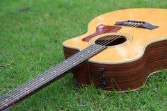 Acoustic guitar in the park. Acoustic guitar on the grass in the park royalty free stock image