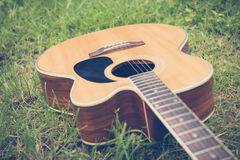 Acoustic guitar on grass with vintage and soft focus Stock Photos