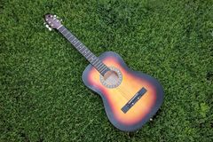 Acoustic guitar in the green grass Stock Photography