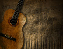 Acoustic Guitar on Grunge Background. Acoustic brown guitar against a grunge brown background Stock Photos