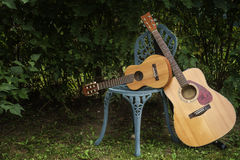 Acoustic guitar and guitalele. On a  green metal chair in garden Royalty Free Stock Photography