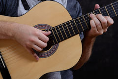 Acoustic guitar guitarist playing details. Musical instrument with performer hands Stock Image