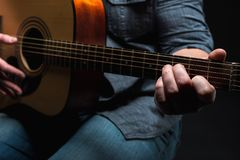Acoustic guitar in the hands of the guy on the whole frame. Horizontal frame Stock Photo