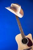 Acoustic Guitar With Hat On Blue Stock Photo