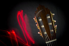 Acoustic guitar head. A close up of acoustic guitar head and red light trails beside it Stock Image