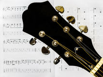 Acoustic guitar - head and tuning keys. A musical instrument. Acoustic guitar and notes Royalty Free Stock Photos