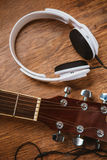 Acoustic guitar and headphone on fabric sofa Stock Image