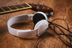 Acoustic guitar and headphone on fabric sofa Royalty Free Stock Image