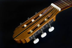 Acoustic guitar headstock. Close-up of a classical acoustic guitar with white machine heads on the headstock Royalty Free Stock Image