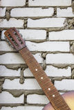 Acoustic guitar headstock against white brick wall Stock Photography