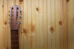 Acoustic guitar headstock against a wooden background Royalty Free Stock Photos