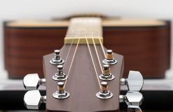 An acoustic guitar headstock on white background. Close up of an acoustic guitar headstock on white background Stock Photography