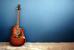 Acoustic Guitar Leaned Against Blue Wall. A brown acoustic guitar leans against a bare blue wall. Photo demonstrates the rule of thirds stock photo