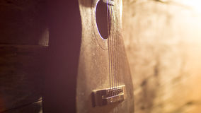 Acoustic guitar leaning on grungy wooden wall Royalty Free Stock Image