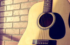 Acoustic Guitar Leaning on Red Brick Wall Close. Acoustic guitar leaning up against an interior red brick wall with nice sunlight shining over it through a royalty free stock photos