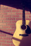Acoustic Guitar Leaning on Red Brick Wall. Acoustic guitar leaning up against an interior red brick wall with nice sunlight shining over it through a nearby royalty free stock photography