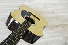 Acoustic guitar. On a light wooden background Stock Images