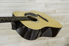 Acoustic guitar. On a light wooden background Royalty Free Stock Photo