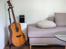 Acoustic guitar in living room. Songwriter concept. Acoustic guitar and loudspeaker on white side table near the sofa with pillows and round glass table on stock images