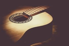 Acoustic guitar lying on a wooden table lit by a beam of light stock photography