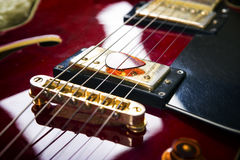 Acoustic guitar with mediator. Red acoustic guitar close up in dark background Royalty Free Stock Photography