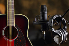 Acoustic guitar, microphone and earphones Stock Photo