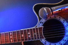 Acoustic guitar and microphone isolated with red and blue lights Stock Photo