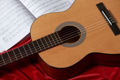 Acoustic guitar and music notes on red fabric, close view of objects Stock Image