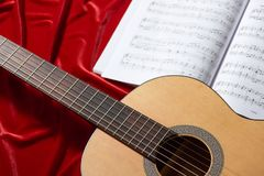 Acoustic guitar and music notes on red fabric, close view of objects Royalty Free Stock Photo