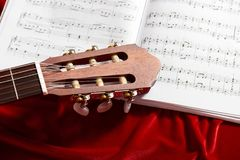 Acoustic guitar and music notes on red velvet fabric, close view of objects stock photo